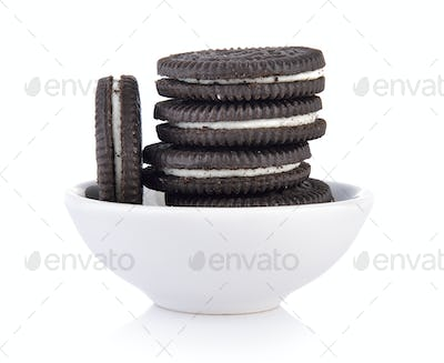 sandwich cookies with cream in bowl on white background