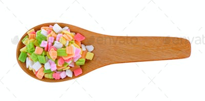 colorful candy in wood spoon on white background