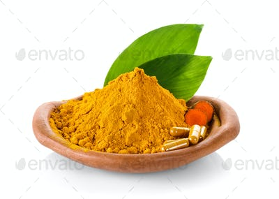 Turmeric powder and turmeric capsules on white background