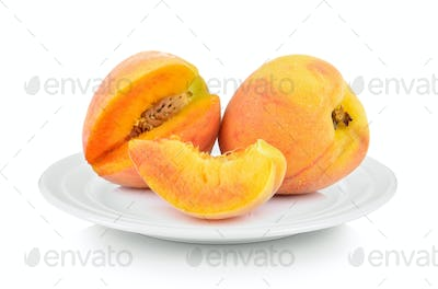 Peach in white plate on white background