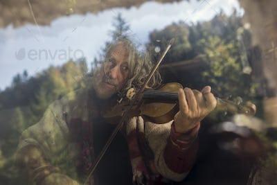 Senior man playing violin behind glass window