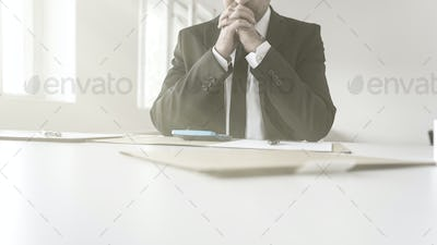 Thoughtful accountant sitting at his desk with paperwork