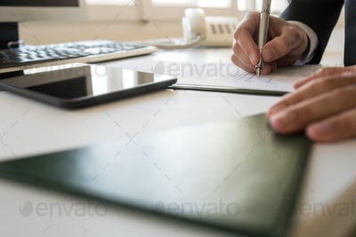 Businessman signing document at his office table in a low angle