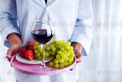girl in a shirt holds a tray of fruit and wine on white background