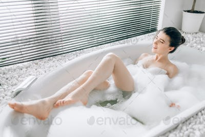 Young woman lying in bath with foam, blured view
