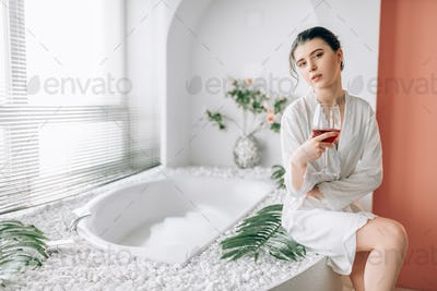Young woman in n white bathrobe, bathroom interior
