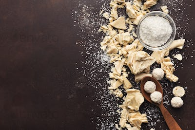 Crushed white chocolate pieces and truffles on dark background
