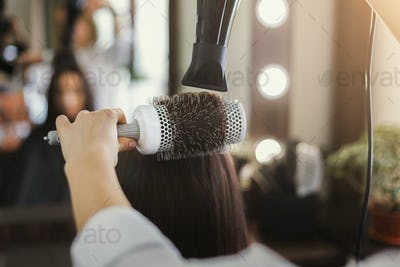 Beautician drying woman's hair