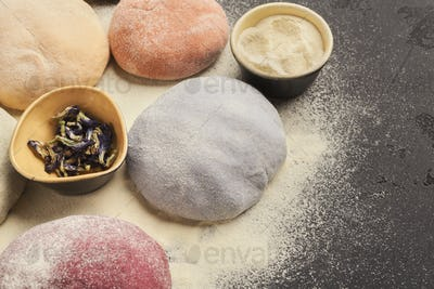 Colorful fresh pasta dough on black table