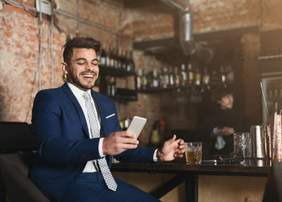 Happy businessman resting in bar after working day
