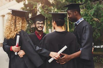 Graduates having a group hug