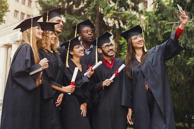 Group of graduates celebrating and making selfie