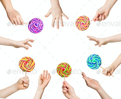 Set of child hands holding lollipops, isolated