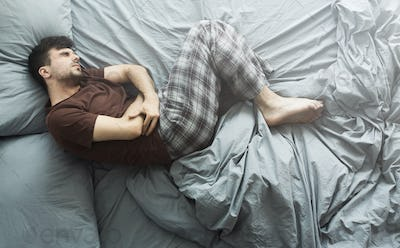 Man lying in bed having abdominal pain, top view
