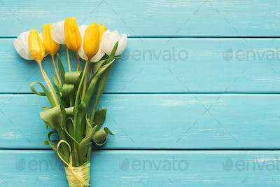 Colorful tulips on blue wooden background, top view