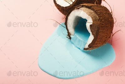 Blue paint running out from coconut on pink background