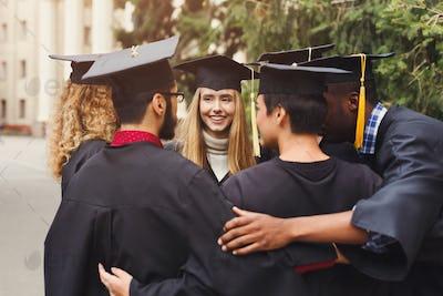 Graduates having group hug on graduation day