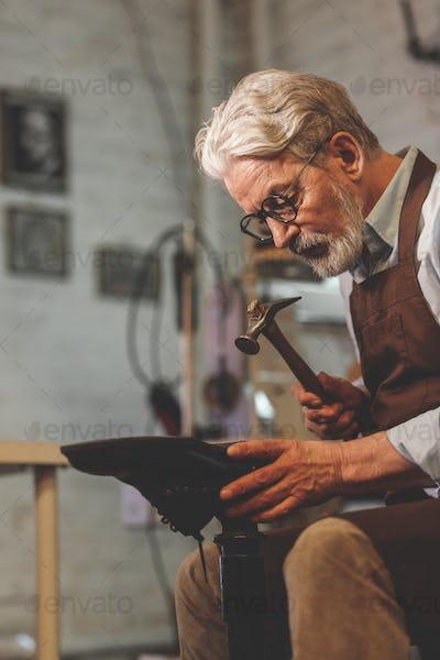 An elderly shoemaker in a studio