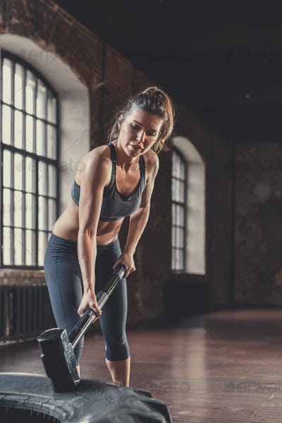 Sports woman with a sledgehammer