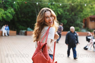 Smiling young woman with backpack walking