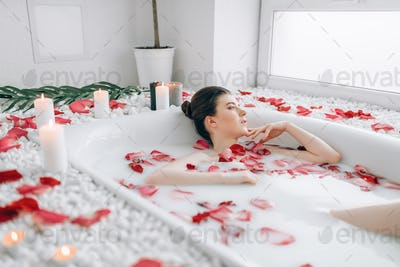 Attractive lady lying in bath with rose petals