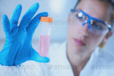 Young female scientist holding liquid sample