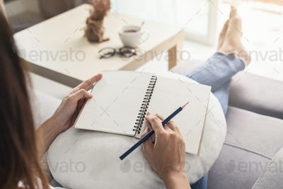 Young woman writing diary at cozy home on sofa in living room