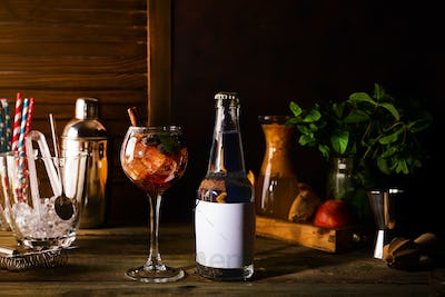 Cocktail with iced tea, whiskey, berries and ice in a glass with a bottle of tonic