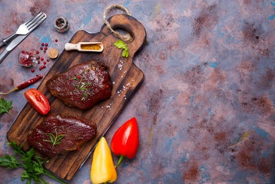 Raw uncooked beef steak meat with pepper spices, Bulgarian pepper and tomato on desk