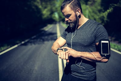 Fit young man setting his sports watch before a run