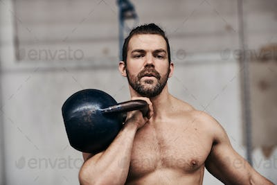 Bare chested young man lifting weights during a gym workout