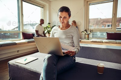 Young businesswoman reading paperwork and working on a laptop