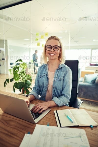 Young businesswoman smiling confidently while sitting at her office desk