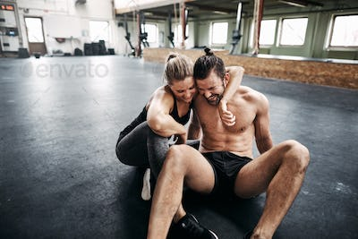 Affectionate young couple sitting in a gym after working out