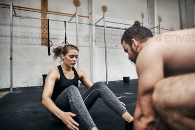 Fit young man helping his female gym partner do crunches