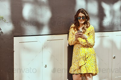 Smiling young woman sending a text message in the city