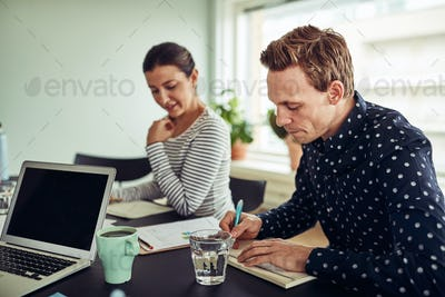 Smiling businesspeople going over paperwork together in an office
