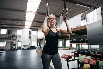 Fit young woman standing in a gym holding rings