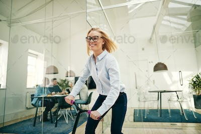 Smiling young businesswoman riding a scooter in an office