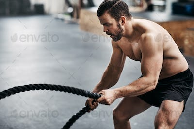 Fit young man swinging ropes during a gym workout