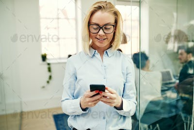 Smiling businesswoman standing in an office sending a text message