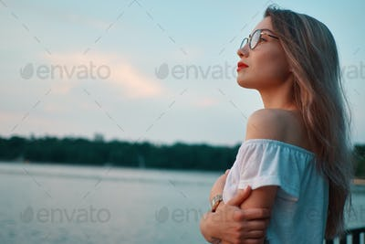 Attractive girl wearing glasses on park lake view
