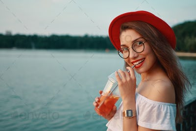 A Young stylish woman having a refreshing drink while looking to