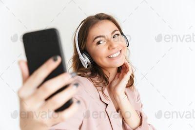 Cute beautiful woman listening music with headphones