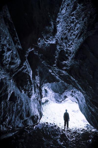 Man at dark cave entrance
