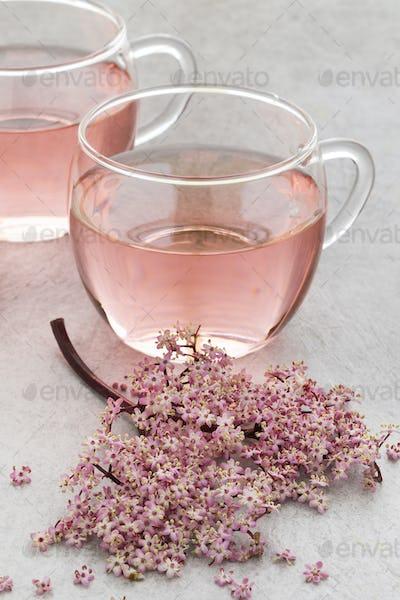 Cup of pink elderberry blossom tea
