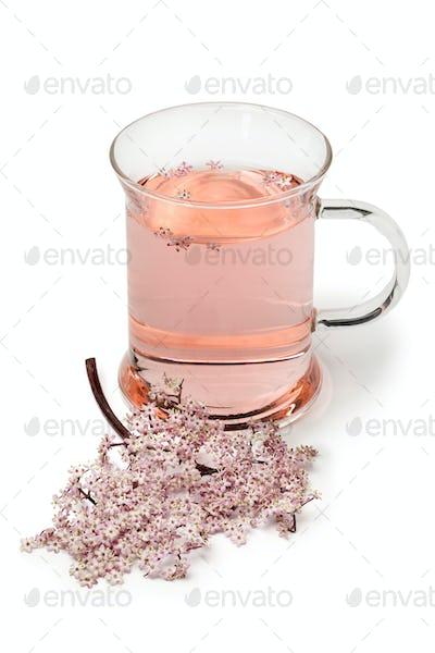 Glass with pink elderberry blossom tea