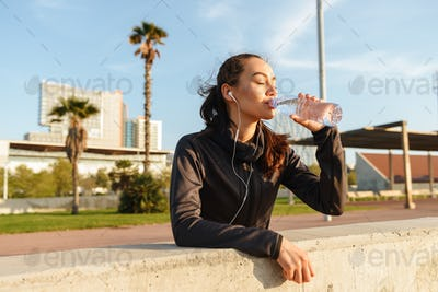 Beautiful young asian sports woman listening music drinking water outdoors.