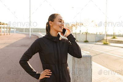 Happy young asian sports woman talking by mobile phone.