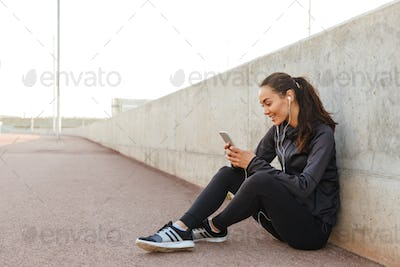 Cheerful young asian sports woman listening music using mobile phone.
